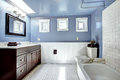 Beautiful lavender bathroom with white wall trim vanity cabinet drawers and mirror bath tub tile Royalty Free Stock Photo