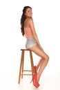 Beautiful leggy woman in stilettos and sexy skimpy shorts posing sitting sideways on a wooden bar stool giving the camera a sultry Stock Image