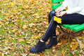 Beautiful legs girl in black pants and boots with yellow leaves in the hands of sitting on the bench in autumn Park Royalty Free Stock Photo