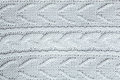 Beautiful light gray knitted pattern, knitted scarf close up. Knitted background Royalty Free Stock Photo