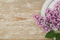 Beautiful lilac flowers lying on a silver saucer against the background of an old wooden plank with a texture paint