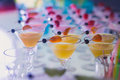 Beautiful line of different colored alcohol cocktails with smoke on a Christmas party, tequila, martini, vodka, and others on part Royalty Free Stock Photo