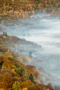 Beautiful Lingering Fog Over Grasmere Lake With Autumnal Colors In Trees. Royalty Free Stock Photo