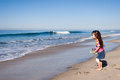 Beautiful little asian girl watching surf anticipation as waits next wave to come Stock Photos