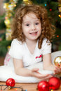 Beautiful little baby girl looking at the camera and smilesâ o on background of of christmas tree Royalty Free Stock Photo