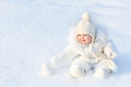 Beautiful little baby girl sitting in white snow