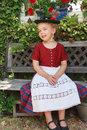 Beautiful little bavarian girl sitting on a sunny bench in the garden in her traditional dirndl apron and hat Stock Image
