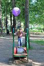 Beautiful little girl with balloon runs on cylinder at playground in summer park Royalty Free Stock Images
