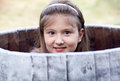 Beautiful little girl in a barrel friendly hiding with just her head peeking out looking at the camera with smile Royalty Free Stock Photography