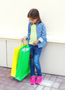Beautiful little girl child with shopping paper bags in city Royalty Free Stock Photo