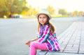 Beautiful little girl child wearing checkered pink shirt and hat in city Royalty Free Stock Photo