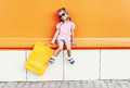 Beautiful little girl child wearing a sunglasses with shopping bags walking in city over colorful orange Royalty Free Stock Photo