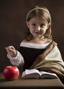 Beautiful little girl Christian, dressed in old clothes, reading the Bible, the hand gestures highlights words and main ideas