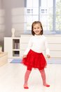 Beautiful little girl dancing smiling in red tutu and red tights in middle of living room Stock Photos