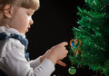 Beautiful little girl decorates the christmas tree black background Royalty Free Stock Photos