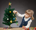 Beautiful little girl decorates the christmas tree dark background Stock Photo