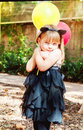 Beautiful little girl dressed as a cat with balloons in hands. Sweet smile, a tender look. Royalty Free Stock Photo