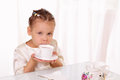 Beautiful little girl drinking cup of tea Royalty Free Stock Image