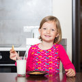 Beautiful little girl drinking milk with cookies selective focus Stock Photography