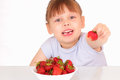 Beautiful little girl gives strawberry Royalty Free Stock Image