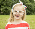 Beautiful little girl with glasses smiling in white Royalty Free Stock Photography