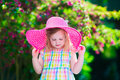 Beautiful little girl in a hat in blooming summer garden Royalty Free Stock Photo