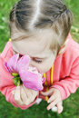 Beautiful little girl inhales the scent of a flower Stock Photo