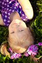 Beautiful little girl lying on the grass in the park smiling ch cute nice child a field with flowers kid rest nature portrait of Stock Photos