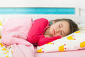 Beautiful little girl in pajamas sleep in bed under blanket Royalty Free Stock Photo