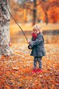 Beautiful little girl playing fishing with a branch and fish toy Royalty Free Stock Photo