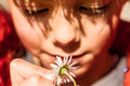 Beautiful little girl playing with flower. Focus on the flower. Royalty Free Stock Photo