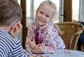 Beautiful little girl playing a game of checkers blond with her young brother sitting looking at the camera with beaming happy Stock Photography