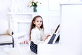 Beautiful little girl playing piano in white living room Royalty Free Stock Photo