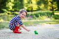 Beautiful little girl in red rain boots playing with rubber frog Royalty Free Stock Photo