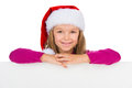 Beautiful little girl in santa claus hat smiling on camera sitting at white table isolated white Stock Photos