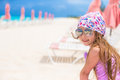 Beautiful little girl sitting on beach chair during summer vacation cute in hat at Stock Image