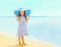 Beautiful little girl in a striped dress and summer straw hat relaxing on the beach near sea