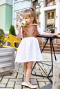 Beautiful little girl wear in fashion dress sitting in a cafe Royalty Free Stock Photo