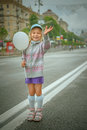 Beautiful little girl with white balloon smiling stands on street of city Royalty Free Stock Image
