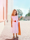 Beautiful little girl in white dress with shopping bag Royalty Free Stock Photo