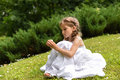 A beautiful little girl in a white long dress sitting on the bright green grass and looking Royalty Free Stock Photo