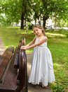 A beautiful little girl in a white long dress staying near the bench in the park with her Royalty Free Stock Photo