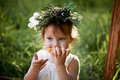 Beautiful little girl in a wreath on the head in green and white. Dress, Princess. With pleasure, but  the nature Royalty Free Stock Photo