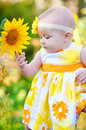 Beautiful little girl in a yellow dress smelling a sunflower Royalty Free Stock Photo
