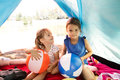 Beautiful little girls in tent camping by the lake. Royalty Free Stock Photo