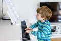 Beautiful little kid boy playing piano in living room or music school Royalty Free Stock Photo