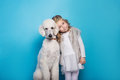 Beautiful little princess with dog. Friendship. Pets. Studio portrait over blue background