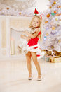Beautiful little santa girl near the christmas tree happy girl beauty with bunny celebrates Royalty Free Stock Images