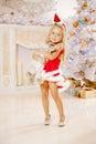 Beautiful little Santa girl near the Christmas tree. Happy girl Royalty Free Stock Photo