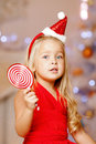 Beautiful little santa girl near the christmas tree happy girl beauty celebrates Royalty Free Stock Photos